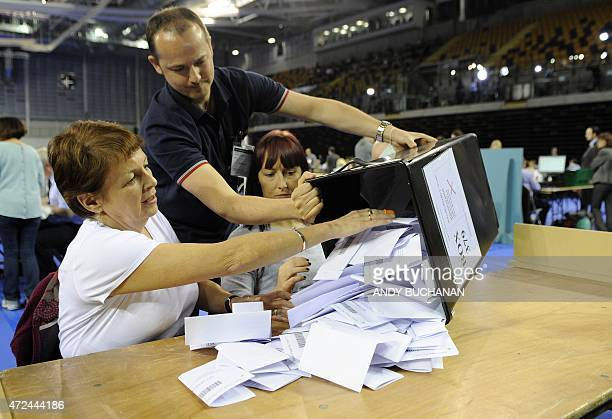 Ballot papers are tipped out onto a table by counting staff at the counting centre at the Emirates Arena in Glasgow on May 7 2015 after the polls...