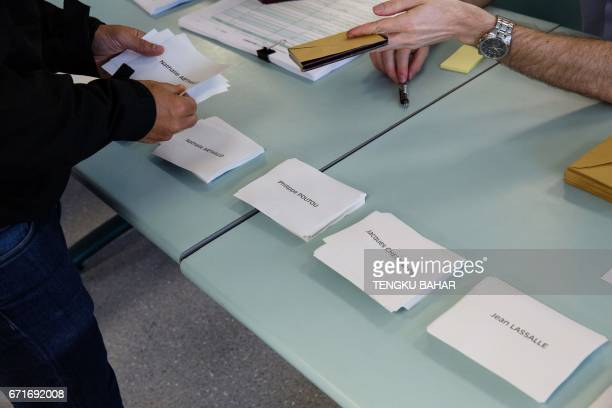 Ballot papers marked with names of presidential candidates are seen as French nationals residing in Hong Kong vote in the first round of France's...