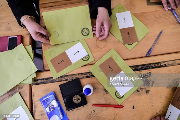 Ballots with the words in Turkish that read 'Evet' or 'Yes' and 'Hayir' or 'No' are prepared as people arrive to vote in the referendum on expanding...