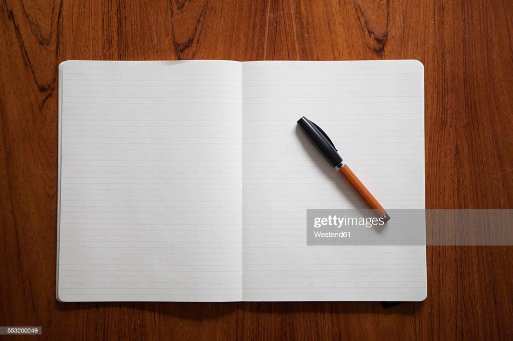 Ballpen lying on opened notebook
