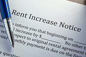 A ballpoint pen rests on top of a notice of an increase in rent.