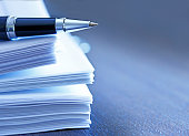 A ballpoint pen rests on top of a stack of documents ready for signing.  The image is photographed using a very shallow depth of field with the focus being on the tip of the pen.