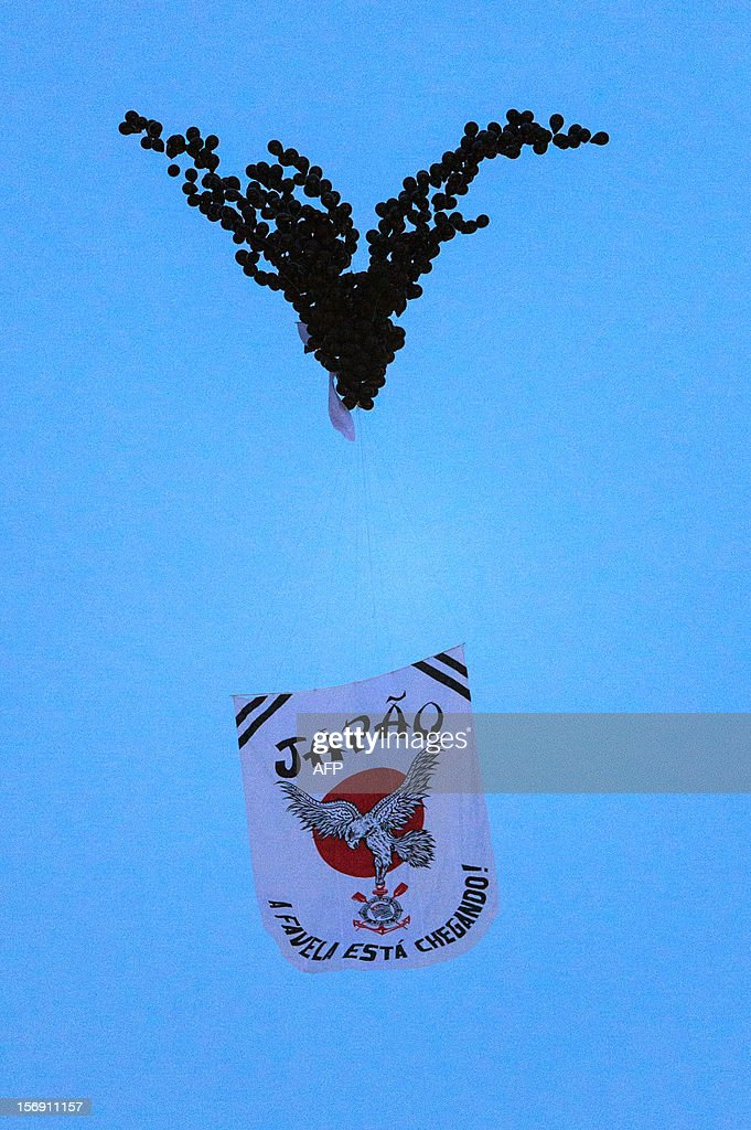 Baloons floated by Fans of Corinthians hold a banner reading 'Japan, the favela (shantytwn) is coming' during their their Brazilian championship football match against Santos at Pacaembu stadium in Sao Paulo, Brazil on Novemeber 24, 2012. Corinthians will play in FIFA Club World Cup in Japan from December 6. AFP PHOTO/Yasuyoshi CHIBA