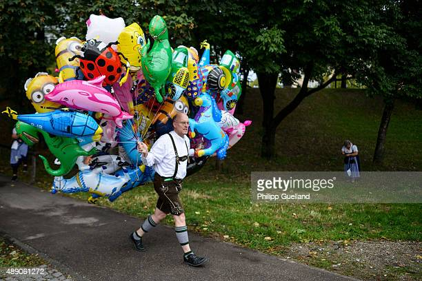 A baloonvendor in bavarian folk attire carries a bunch of helium baloons on the opening day of the 2015 Oktoberfest on September 19 2015 in Munich...