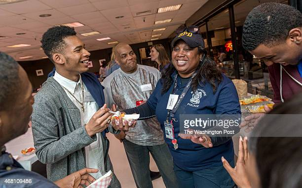 Baltimore City Police Officer Wanda S Alston center in hat who graduated from Edmondson High School in 1976 argues about who wen to the best high...