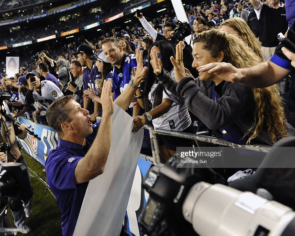 Baltimore head coach John Harbaugh, left, high fives fans after the Ravens game against San Diego at Qualcomm Stadium on Sunday, November 25, 2012, in San Diego, California. The Baltimore Ravens defeated the San Diego Chargers, 16-13 in overtime.