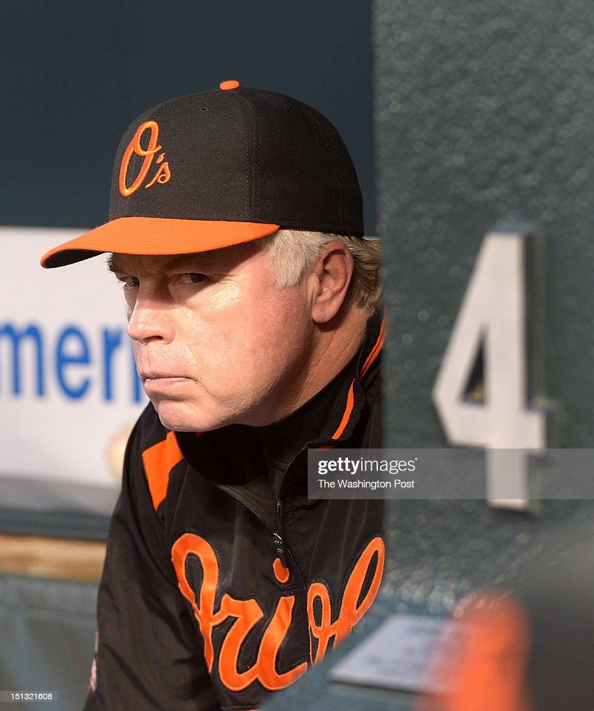 Baltimore Orioles manager Buck Showalter (26) keeps an eye on the action as his team takes on the Toronto Blue Jays on August 24, 2012 in Baltimore, MD. The #4 is for legendary Orioles manager Earl Weaver.