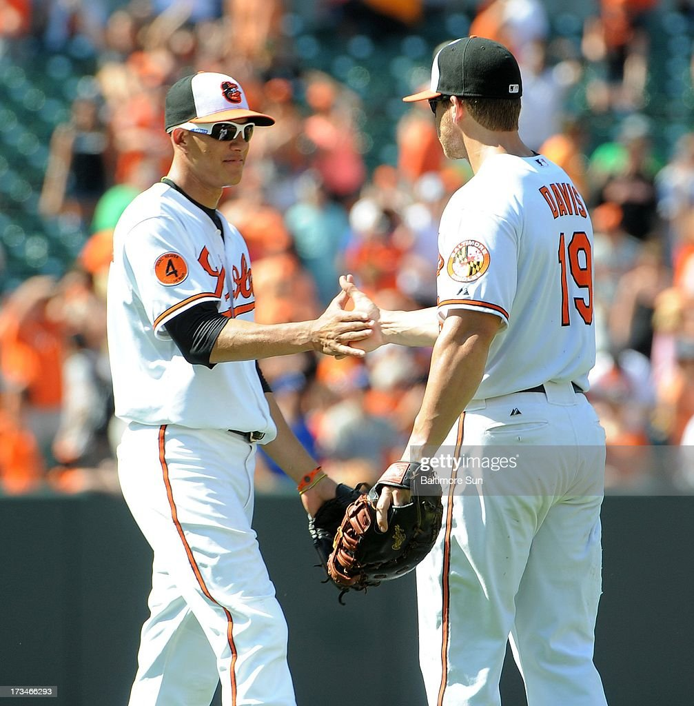 Baltimore Orioles' Manny Machado, left, congratulates teammate Chris Davis after their 7-4 win over the Toronto Blue Jays at Oriole Park at Camden Yards in Baltimore, Maryland, Sunday, July 14, 2013.