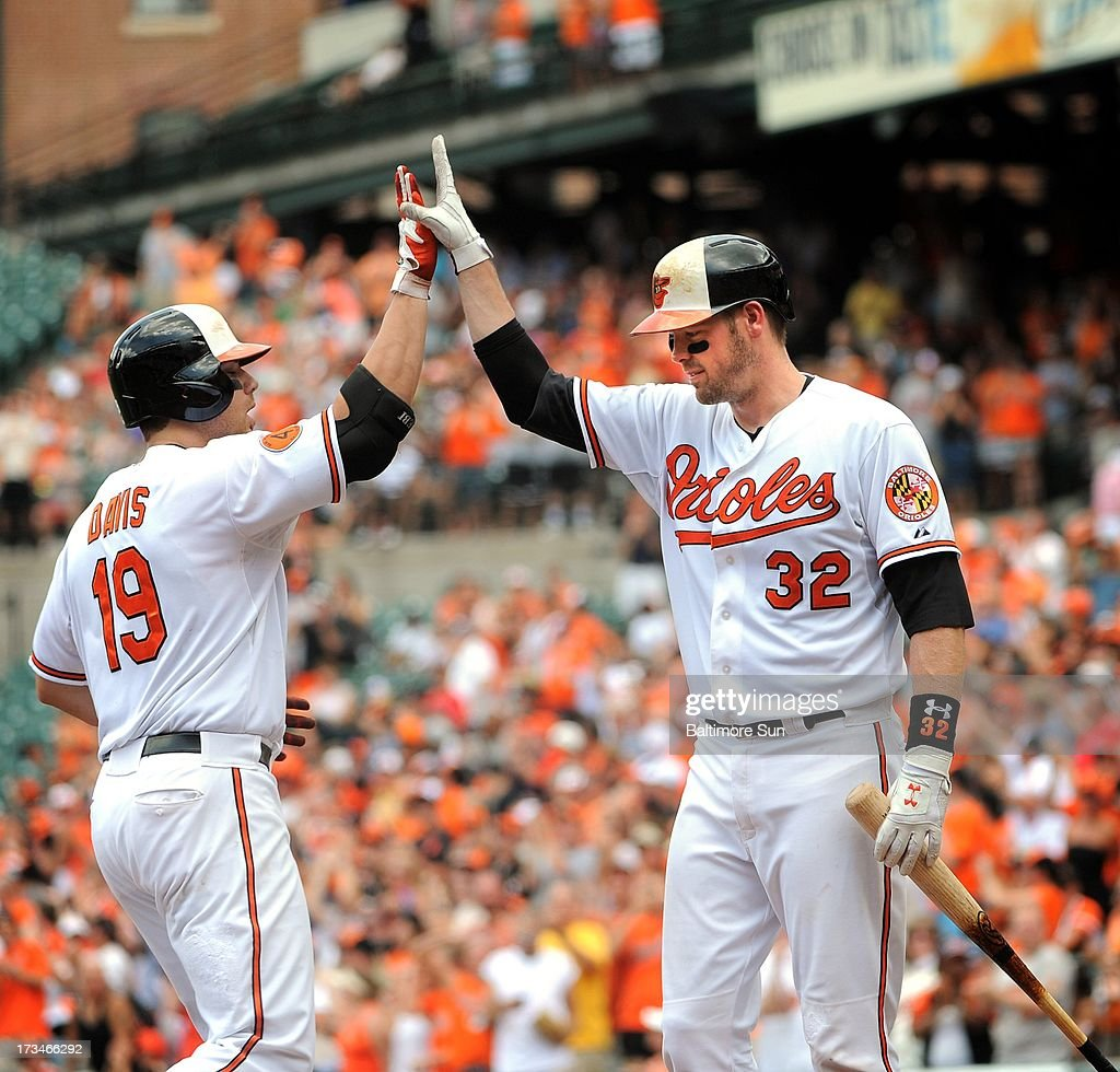 Baltimore Orioles' Matt Wieters congratulates Chris Davis on scoring against the Toronto Blue Jays in the first inning at Oriole Park at Camden Yards in Baltimore, Maryland, Sunday, July 14, 2013.