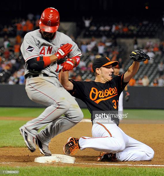 Baltimore Orioles pitcher Chris Ray beats Los Angeles Angels Maicer Izturis to the bag at first while catching a throw from Brian Roberts to end the...