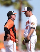 Baltimore Orioles pitching coach Dave Wallace talks with pitcher Alfredo Aceves during the eighth inning of the game against the Boston Red Sox at Ed...