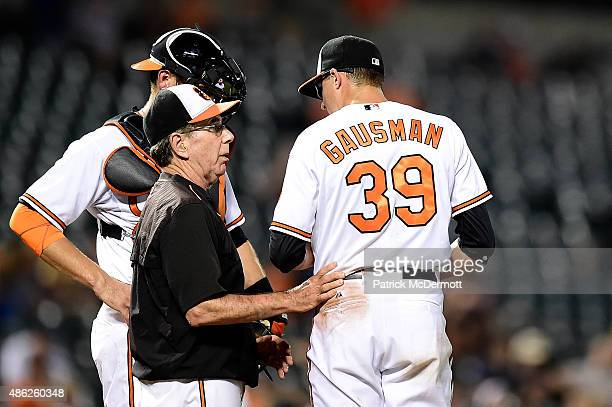 Baltimore Orioles pitching coach Dave Wallace talks with starting pitcher Kevin Gausman in the top of the third inning during a baseball game against...