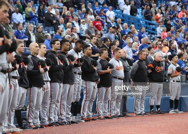 Baltimore Orioles players and coaches stand in front of their dugout as they observe a moment of silence on the sixteenth anniversary of 9/11 before...