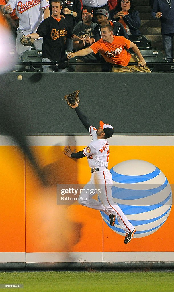 Baltimore Orioles right fielder Nick Markakis leaps in vain as a drive hit by the Tampa Bay Rays' James Loney clears the wall for a solo home run off to tie the game in the eighth inning at Oriole Park at Camden Yards on Thursday, April 18, 2013, in Baltimore, Maryland. The Orioles won, 10-6, in 10 innings.