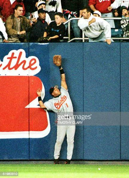 Baltimore Orioles' right fielder Tony Tarasco trioes to catch a fly ball from the New York Yankees' Derek Jeter 09 October but the ball is caught by...