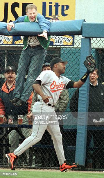 Baltimore Orioles rightfielder Joe Carter takes away a hit from Chicago White Sox Frank Thomas and the ball from an overeager fan during the 8th...