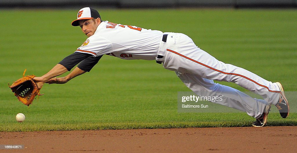 Baltimore Orioles shortstop J.J. Hardy dives for a grounder hit by the Tampa Bay Rays' James Loney for a base hit at Oriole Park at Camden Yards on Thursday, April 18, 2013, in Baltimore, Maryland. The Orioles won, 10-6, in 10 innings.