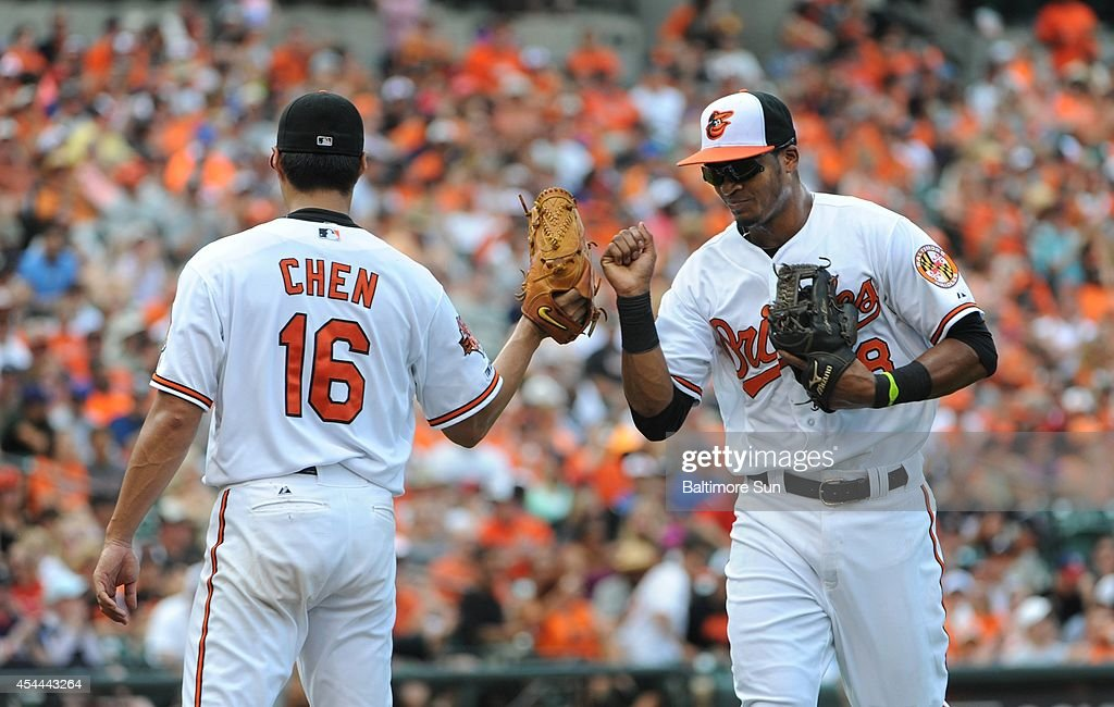 Baltimore Orioles starting pitcher Wei-Yin Chen, left, gets a fist bump from third baseman Jimmy Paredes during the third inning of their game against the Minnesota Twins on Sunday, Aug. 31, 2014, at Camden Yards in Baltimore.