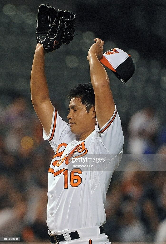 Baltimore Orioles starting pitcher Wei-Yin Chen (16) stretches to cool himself after yielding a two-run homer against the New York Yankees during the second inning at Oriole Park at Camden Yards in Baltimore, Maryland, Thursday, September 12, 2013.
