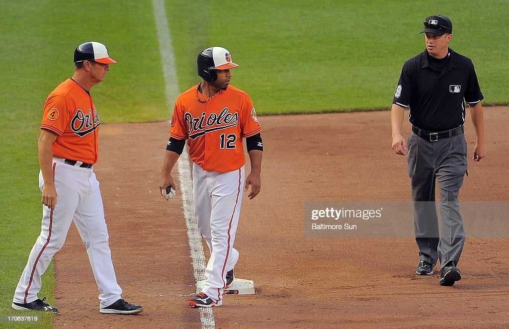 Baltimore Orioles third base coach Bobby Dickerson, left, watches as umpire Cory Blaser speaks to pinch runner Alexi Casilla (12) who, standing on third, was called out after being doubled up at first base on a fly out hit by batter Ryan Flaherty to end the game at Oriole Park at Camden Yards on Saturday, June 15, 2013, in Baltimore, Maryland. The Boston Red Sox held on for a 5-4 win.