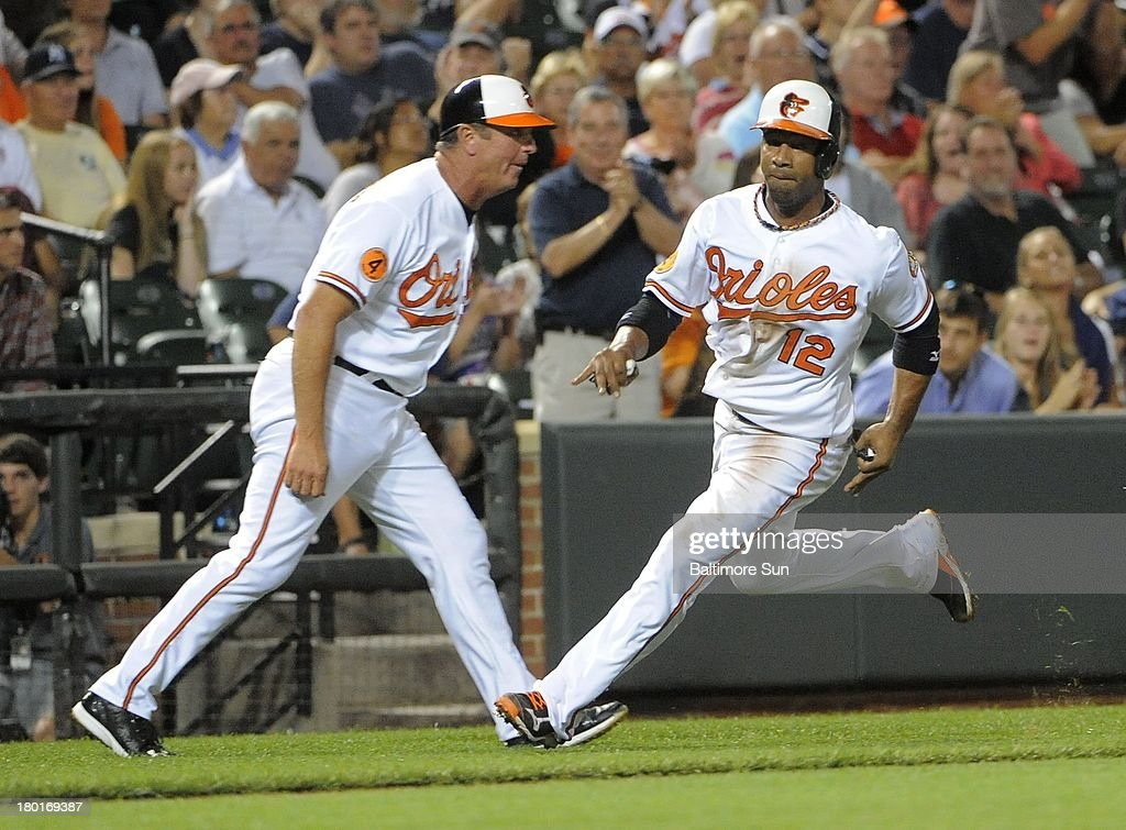 Baltimore Orioles third base coach Bobby Dickerson waves Orioles' Alexi Casilla home on a single by Orioles' Nick Markakis in the fifth inning against the New York Yankees at Oriole Park at Camden Yards in Baltimore, Maryland, Monday, September 9, 2013.