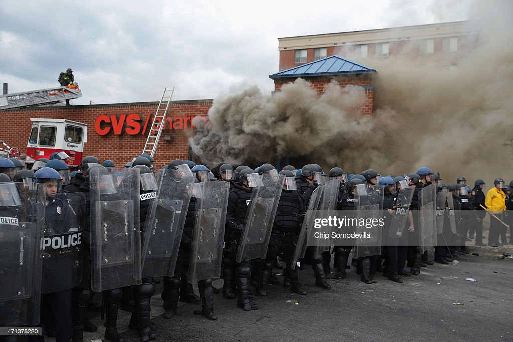 Baltimore Police form a parimeter around a CVS pharmacy that was looted and burned near the corner of Pennsylvania and North avenues during violent protests following the funeral of Freddie Gray April 27, 2015 in Baltimore, Maryland. Gray, 25, who was arrested for possessing a switch blade knife April 12 outside the Gilmor Homes housing project on Baltimore's west side. According to his attorney, Gray died a week later in the hospital from a severe spinal cord injury he received while in police custody.