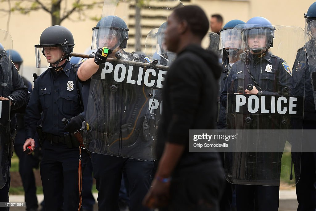 Baltimore Police officer aims his taser at a demonstrator outside the Mondawmin Mall following the funeral of Freddie Gray April 27 2015 in Baltimore...