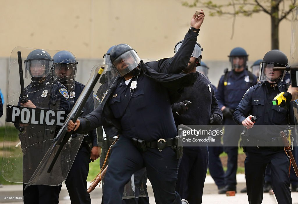 Baltimore Police officer throws a rock back at violent protesters outside the Mondawmin Mall following the funeral of Freddie Gray April 27 2015 in...
