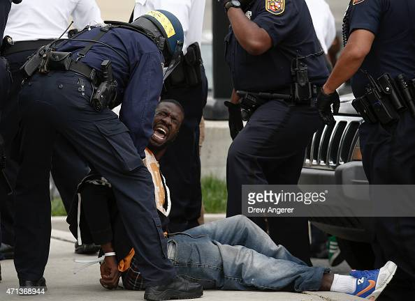 Baltimore Police officers arrest a man near Mowdamin Mall April 27 2015 in Baltimore Maryland The funeral service for Freddie Gray who died last week...