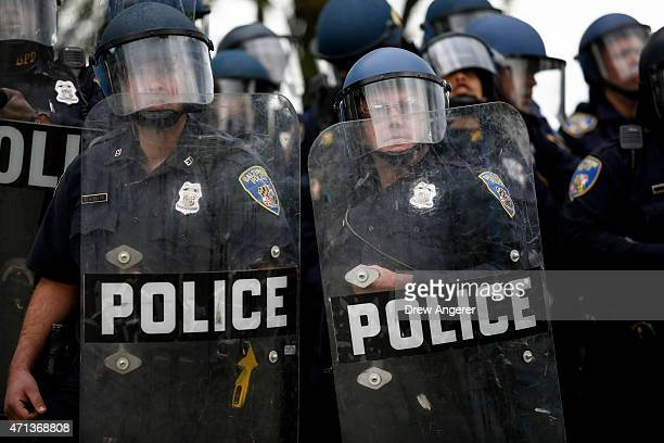 Baltimore Police officers in riot gear look toward protestors along Reisterstown Road near Mondawmin Mall April 27 2015 in Baltimore Maryland A group...