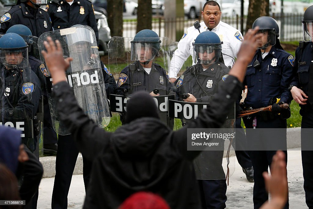 Baltimore Police officers in riot gear stand in formation near protestors along Reisterstown Road near Mondawmin Mall April 27 2015 in Baltimore...