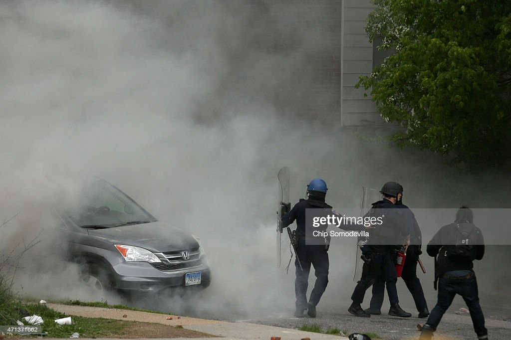 Baltimore Police officers use tear gas to disperse protesters outside the Mondawmin Mall following the funeral of Freddie Gray April 27 2015 in...