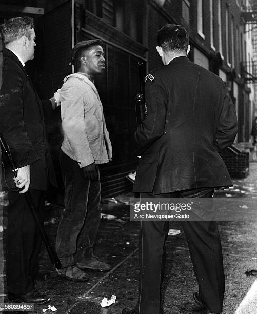 Baltimore Police officers with billy clubs and shotgun arresting a young AfricanAmerican protester during the aftermath of a riot at Franklin Street...