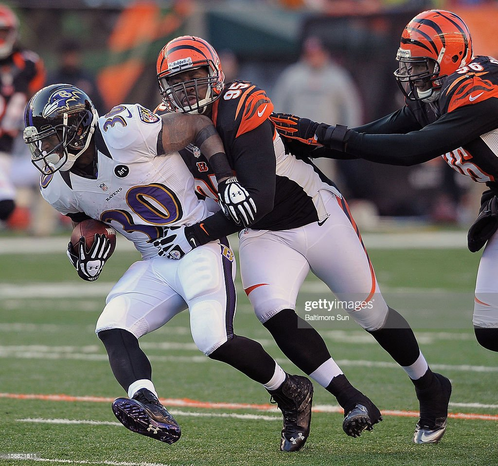 Baltimore Ravens' Bernard Pierce is dropped for a 2-yard loss by Cincinnati Bengals' Wallace Gilbery (95) and Carlos Dunlap (96) at Paul Brown Stadium on Sunday, December 30, 2012, in Cincinnati, Ohio. Pierce appeared to hurt his ankle and left the game. The Cincinnati Bengals defeated the Baltimore Ravens, 23-17.
