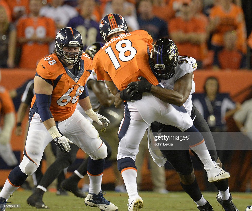 Baltimore Ravens defensive tackle Chris Canty (99) puts a hit on Denver Broncos quarterback Peyton Manning (18) as he throws a touchdown pass in the second quarter. The Denver Broncos took on the Baltimore Ravens in the first game of the 2013 season at Sports Authority Field at Mile High in Denver on September 5, 2013.