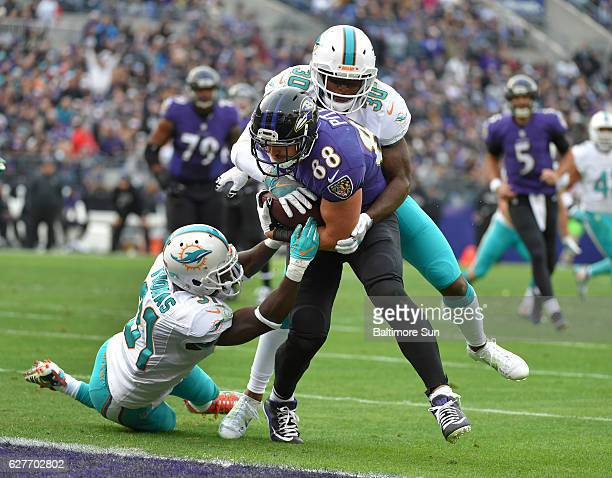 Baltimore Ravens' Dennis Pitta scores a second quarter touchdown as Miami Dolphins' Bacarri Rambo and Michael Thomas can't stop him from scoring on...