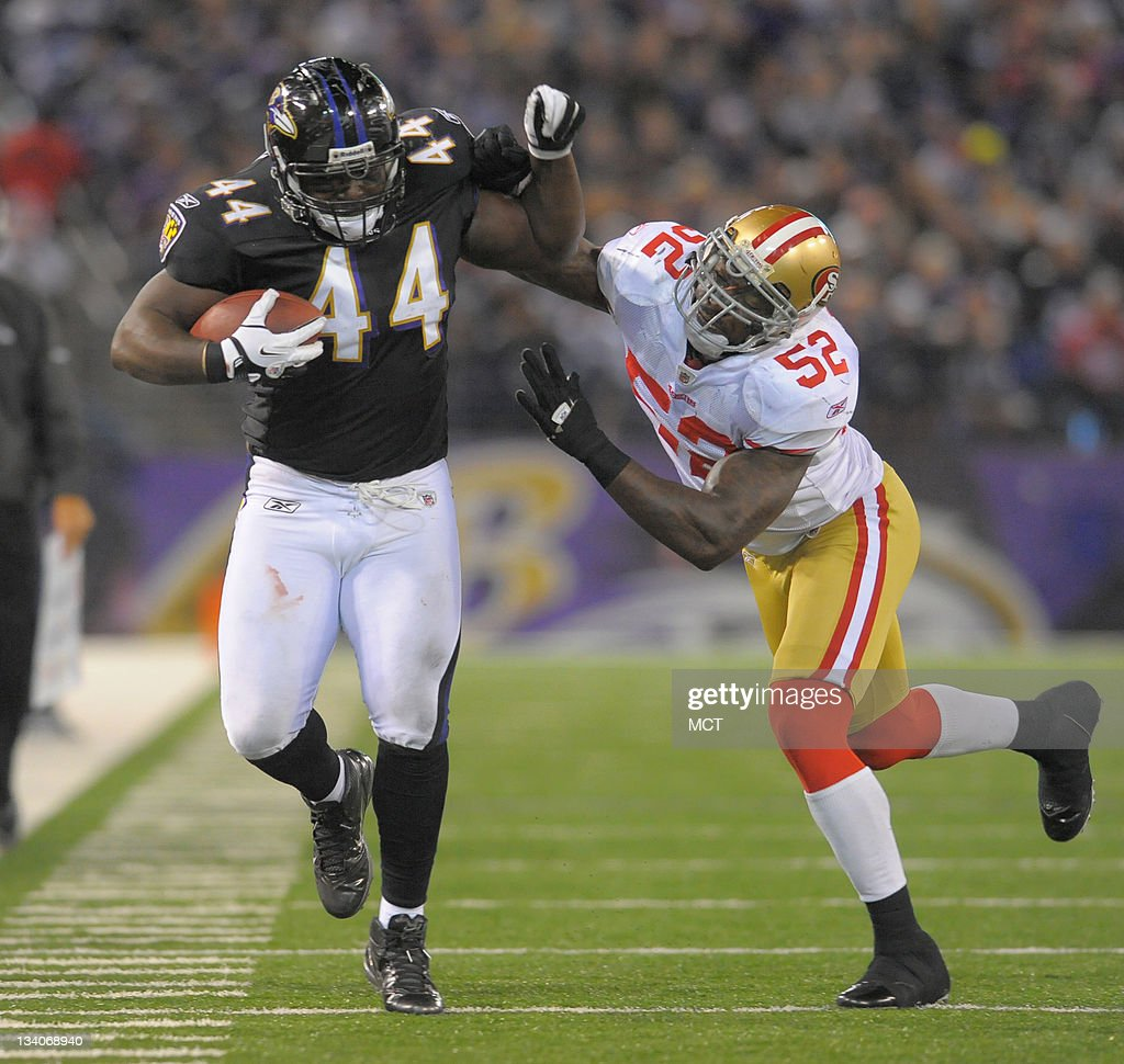 Baltimore Ravens fullback Vonta Leach fends off San Francisco 49ers inside linebacker Patrick Willis as he picks up a first down following a...