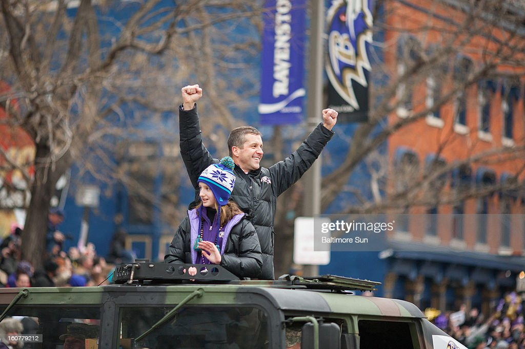 Baltimore Ravens head coach John Harbaugh and his daughter, Alison, wave to fans during a parade in Baltimore, Maryland, Tuesday, February 5, 2013.