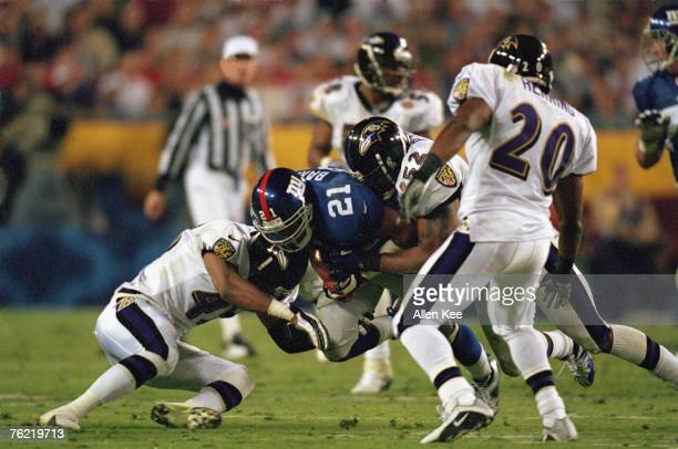 Baltimore Ravens linebacker Ray Lewis and safety Corey Harris tackle New York Giants running back Tiki Barber in Super Bowl XXXV on Lewis was named...
