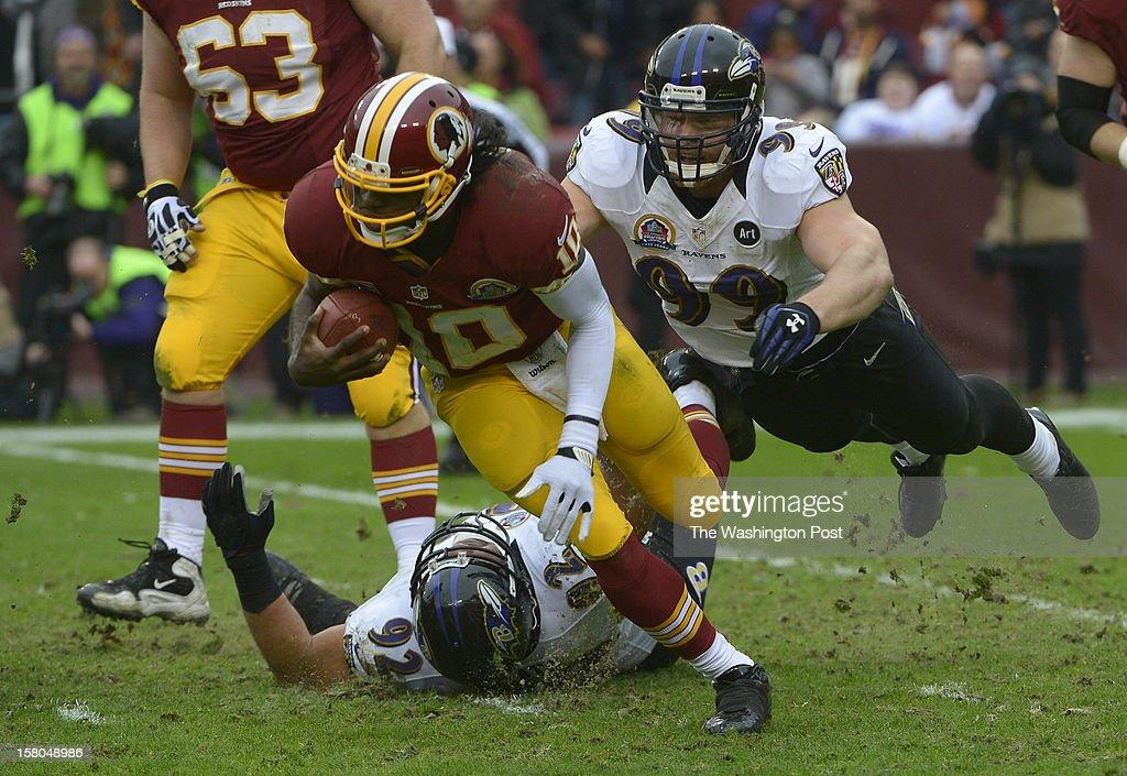 Baltimore Ravens outside linebacker Paul Kruger (99) dives for Washington Redskins quarterback Robert Griffin III (10) and a first-quarter sack during a game between the Baltimore Ravens and Washington Redskins at FedEx Field on December 9, 2012 in Landover, Md.