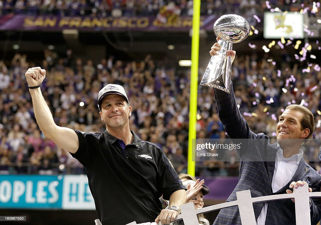 Baltimore Ravens owner Steve Bisciotti (R) and head coach John Harbaugh (L) celebrate with the Vince Lombardi championship trophy on the podium after the Ravens won 34-31 against the San Francisco 49ers during Super Bowl XLVII at the Mercedes-Benz Superdome on February 3, 2013 in New Orleans, Louisiana.