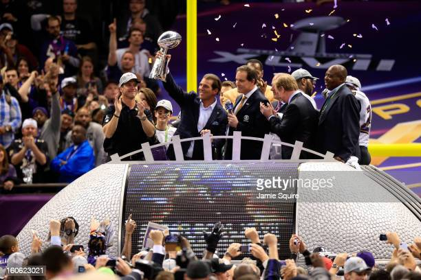 Baltimore Ravens owner Steve Bisciotti holds up the Vince Lombardi Trophy in front of head coach John Harbaugh and CBS host Jim Nantz during Super...