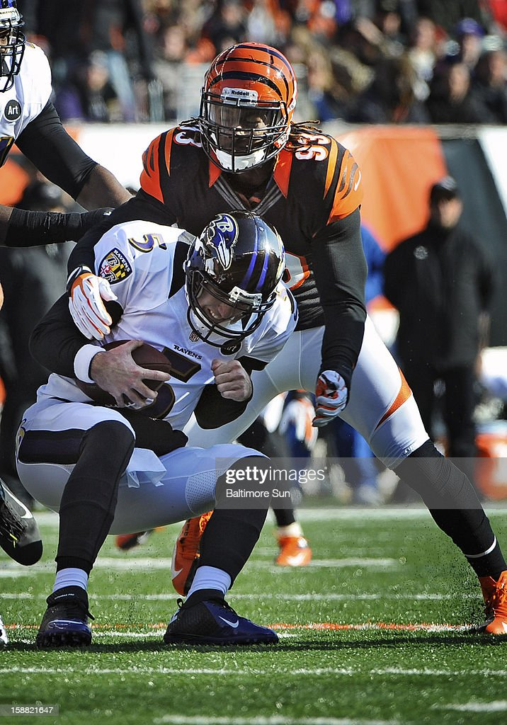 Baltimore Ravens quarterback Joe Flacco (5), bottom is sacked by Cincinnati Bengals' Michael Johnson (93), top, for a 7-yard loss in the first quarter at Paul Brown Stadium on Sunday, December 30, 2012, in Cleveland, Ohio. The Cincinnati Bengals defeated the Baltimore Ravens, 23-17.