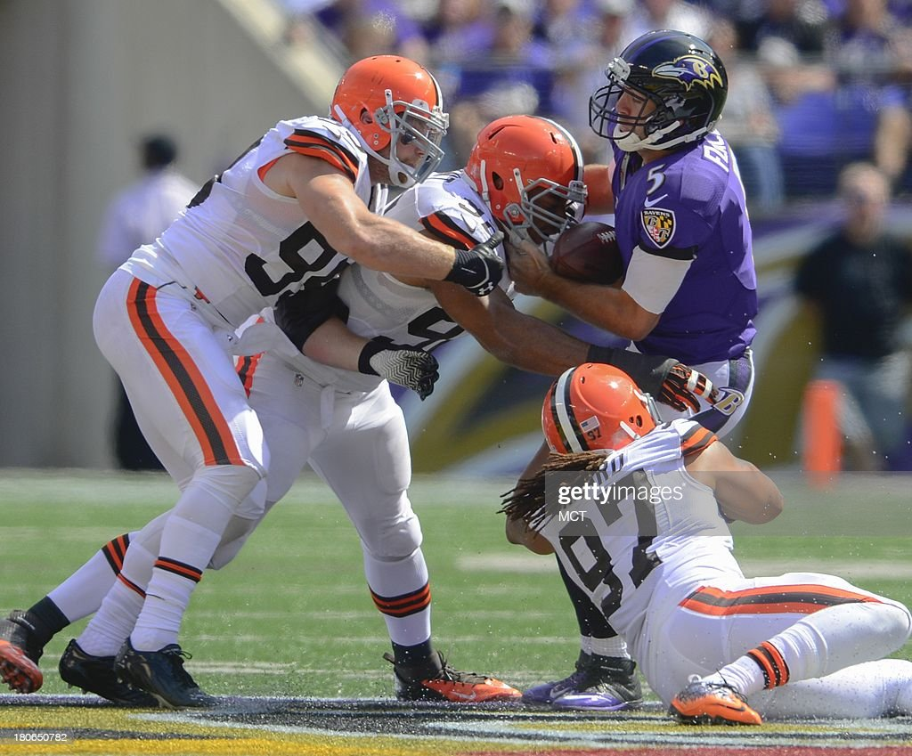 Baltimore Ravens quarterback Joe Flacco is saved by Cleveland Browns defensive end Desmond Bryant (92), outside linebackers Paul Kruger (99) and Jabaal Sheard (97) during the first half of their game on Sunday, September 15, 2013, in Baltimore, Maryland.