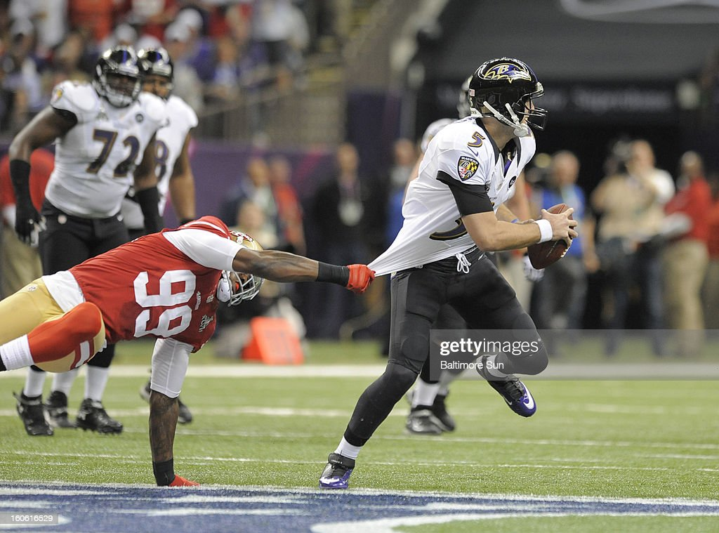 Baltimore Ravens quarterback Joe Flacco (5) rolls out of the pocket to avoid San Francisco 49ers' Aldon Smith (99) during first-half action in Super Bowl XLVII at the Mercedes-Benz Superdome in New Orleans, Louisiana, Sunday, February 3, 2013.