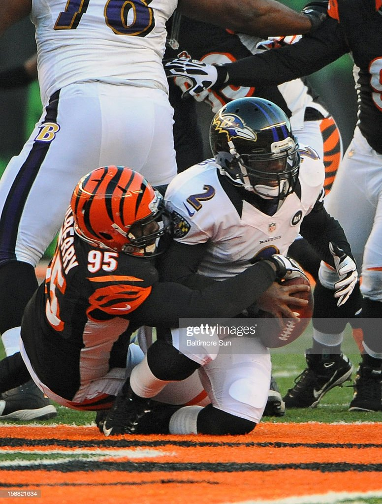 Baltimore Ravens quarterback Tyrod Taylor (2), right, is sacked by Cincinnati Bengals' Wallace Gilberry (95) for a 10-yard loss in the fourth quarter at Paul Brown Stadium on Sunday, December 30, 2012, in Cleveland, Ohio. The Cincinnati Bengals defeated the Baltimore Ravens, 23-17.