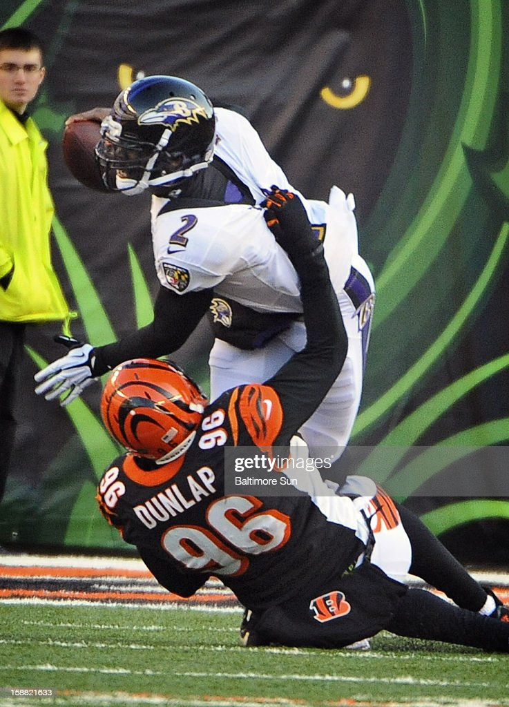 Baltimore Ravens quarterback Tyrod Taylor (2), top, is sacked by Cincinnati Bengals' Carlos Dunlap (96), bottom, for a loss of 13 yards in the third quarter at Paul Brown Stadium on Sunday, December 30, 2012, in Cleveland, Ohio. The Cincinnati Bengals defeated the Baltimore Ravens, 23-17.