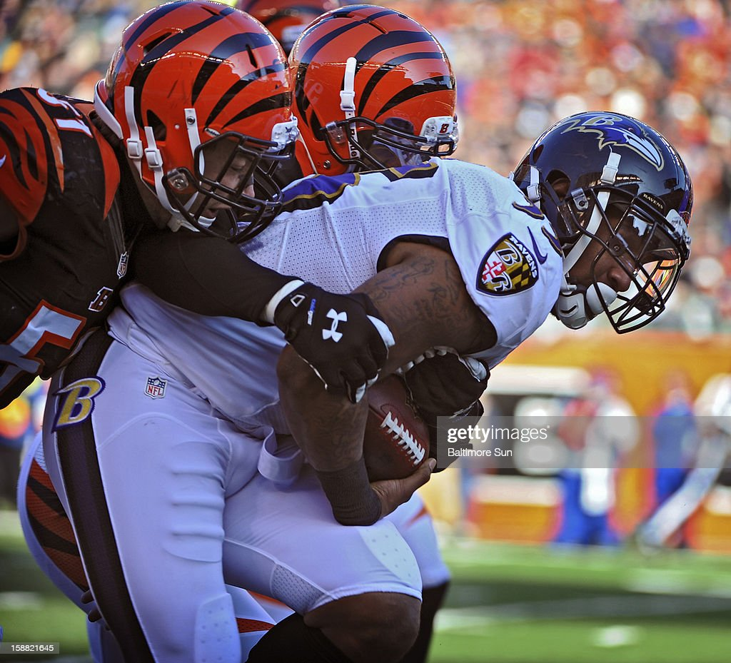 Baltimore Ravens running back Anthony Allen, right, ran 20 yards before getting tackled by Cincinnati Bengals' Dan Skuta, left, and Taylor Mays in the first quarter at Paul Brown Stadium on Sunday, December 30, 2012, in Cleveland, Ohio. The Cincinnati Bengals defeated the Baltimore Ravens, 23-17.