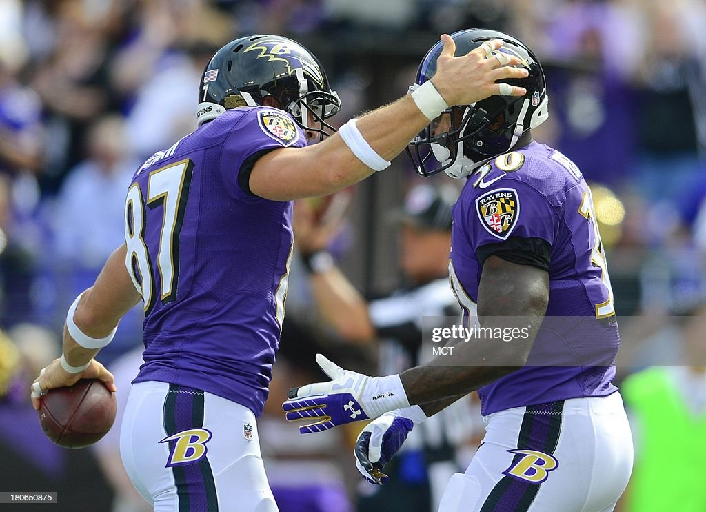 Baltimore Ravens running back Bernard Pierce (right) gets congratulations from teammate Dallas Clark after scoring his team's first touchdown during the second half of their game on Sunday, September 15, 2013, in Baltimore, Maryland.