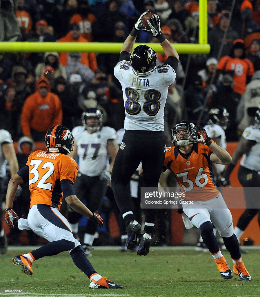 Baltimore Ravens tight end Dennis Pitta makes a catch between the defense of Denver Broncos cornerback Tony Carter, left, and free safety Jim Leonhard during overtime in the AFC Divisonal Playoff at Sports Authority Field at Mile High in Denver, Colorado, on Saturday, January 12, 2013. Baltimore won in OT, 38-35.